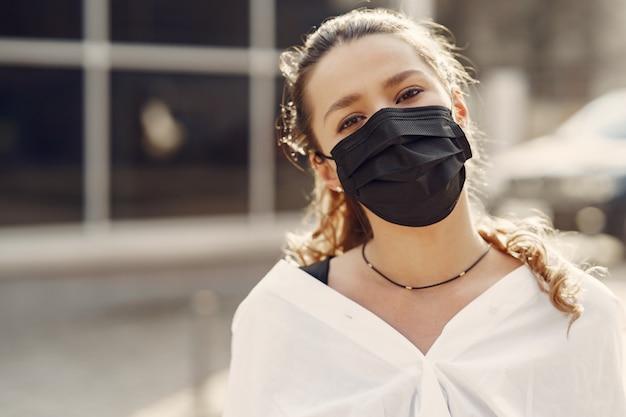 Женщина в маске стоит на улице