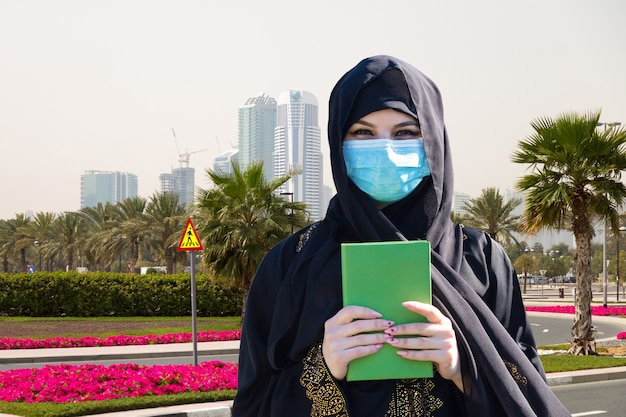 現代の都市を背景にコーランを手にしたマスクの女性。