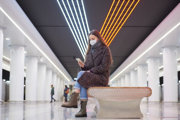 의료 얼굴 마스크를 쓴 여성이 스마트 폰으로 큰 지하철역 중앙에 앉아 뉴스를 읽고 있습니다.