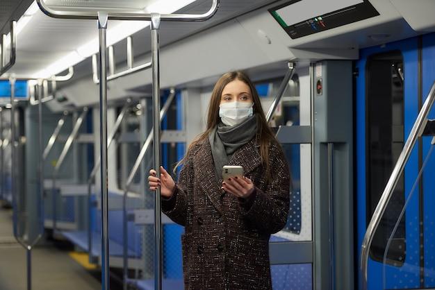 코로나 바이러스의 확산을 피하기 위해 의료용 마스크를 쓴 여성이 현대 지하철 차량에서 스마트 폰을 들고 서 있습니다.