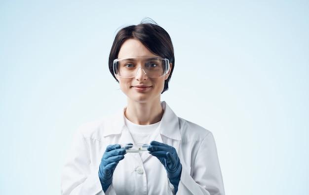 의료 가운과 안경에 여자는 그녀의 손 생물학 식물학 의학에 식물 플라스크를 보유하고 있습니다.