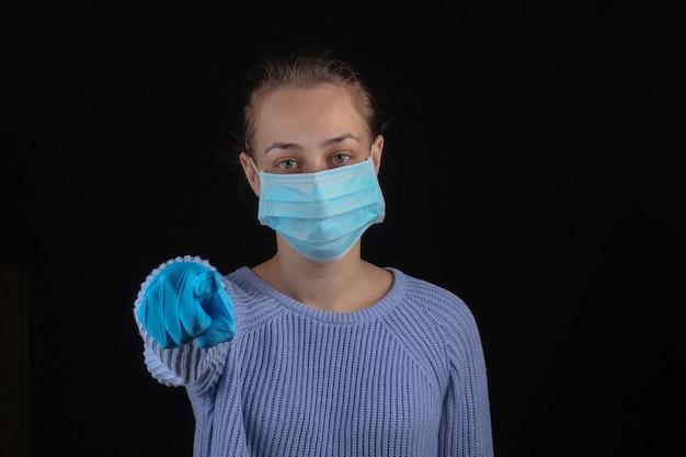 의료 마스크와 장갑에 여자는 검은 벽에 당신을 가리 킵니다.