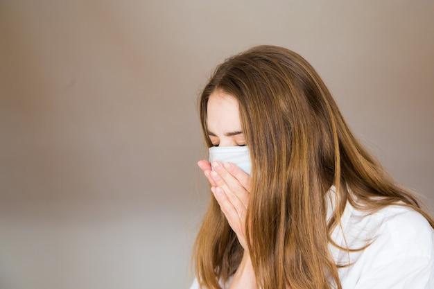 Женщина в медицинской маске на белом фоне в медицинской маске. пациент кашляет