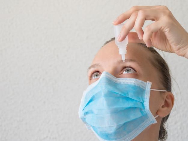 Женщина в медицинской маске, используя глазные капли. профилактика вирусных инфекций
