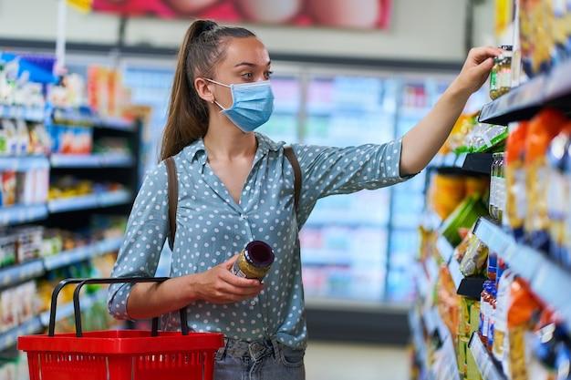 医療用防護マスクを着た女性が食料品店の棚から食品を選んで取る