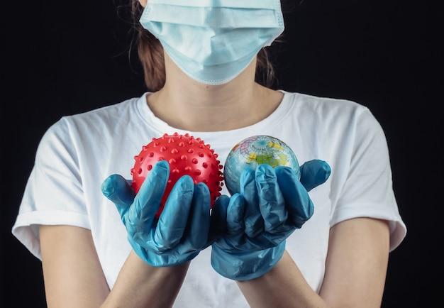 의료 보호 마스크에 여자, 장갑은 검은 벽에 글로브와 바이러스 변형 모델을 개최합니다.