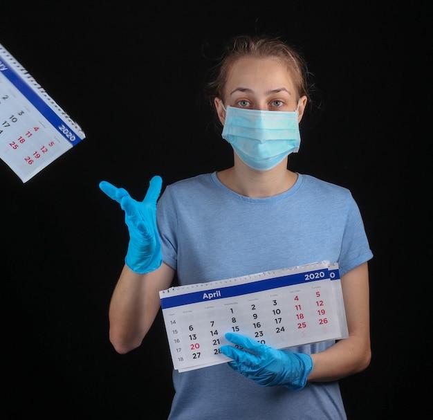 医療防護マスクの女性、手袋は黒い壁に毎月のカレンダーを保持します。検疫、パンデミックcovid-19