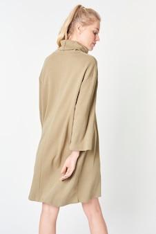 최소한의 베이지 색 드레스 모형에있는 여자