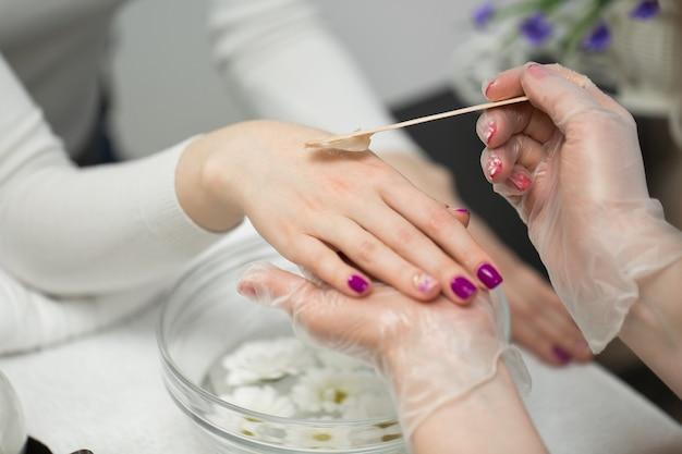 マニキュアを受けているネイルサロンの女性、彼女はパラフィンまたはワックスで手を浴びています
