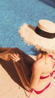 수영장 옆에 앉아 있는 분홍색 비키니를 입은 여자 휴대폰 벽지
