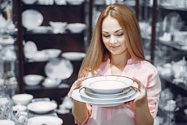 Женщина в розовой блузке покупает посуду в магазине