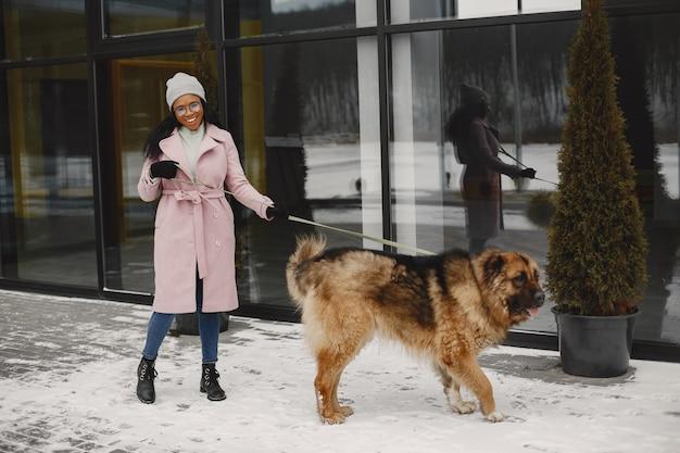 犬とピンクのコートを着た女性