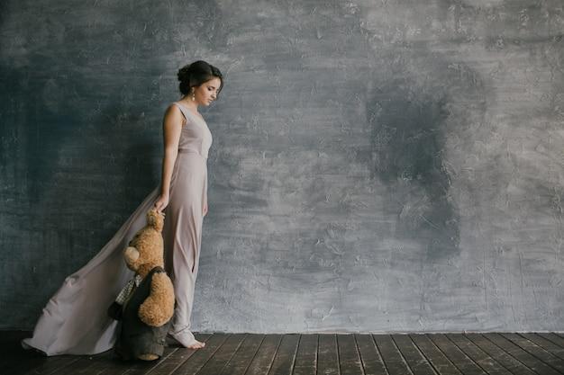 ピンクのドレスを着た女性が灰色の壁の横を歩き、テディベアを抱えています