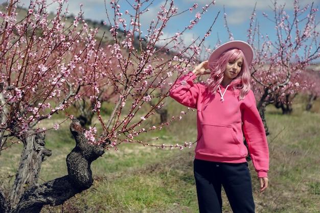 ピンクのパーカーと髪のかつらの女性はクリミア半島の春に花と桃畑に立っています