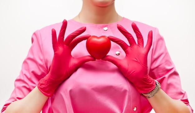 손에 마음을 잡고 분홍색 의료 제복을 입은 여자