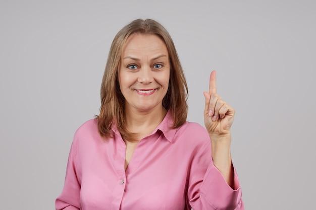 ピンクのシャツを着た女性が人差し指を上にして手を握る