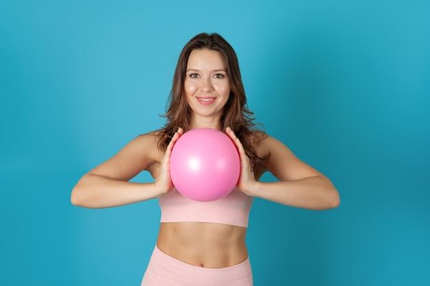 ピラティスボールを握りしめているピンクのスポーツトップの女性