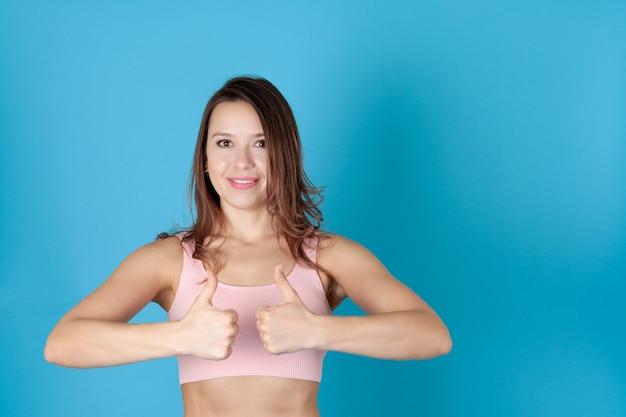 親指を立てるピンクのスポーツトップの女性