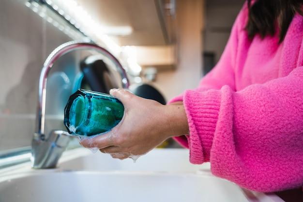 青いガラスの内側を洗うピンクのセーターの女性