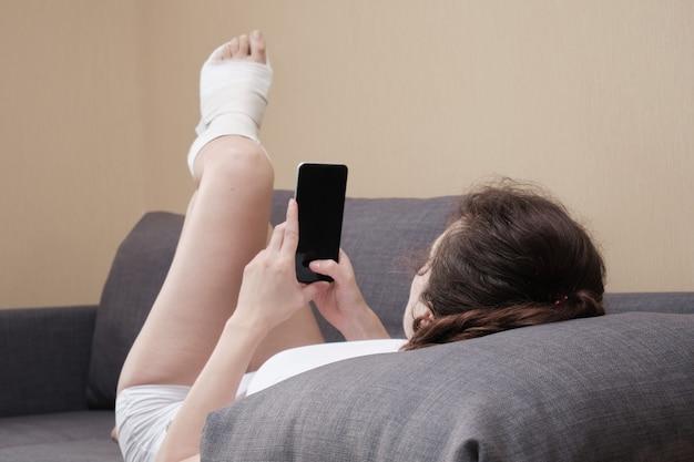석고 깁스를 한 여성이 집에 있는 소파에 누워 스마트폰을 사용하고 있습니다.
