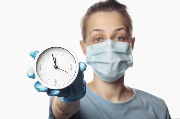保護マスクの女性、手袋は白で隔離される白い時計を保持します