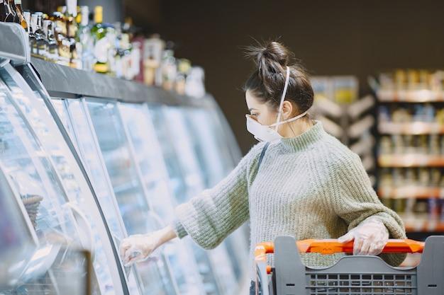 Женщина в защитной маске в супермаркете