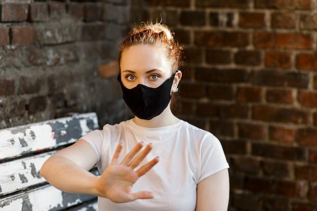 防護マスクを着た女性がコロナウイルスの流行の発生を止めるために手の一時停止の標識を示しています
