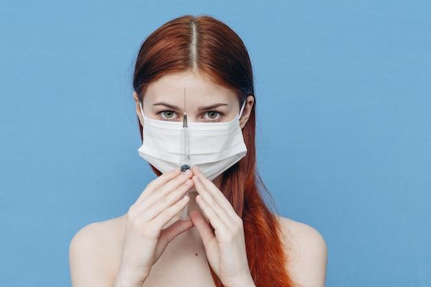 注射器で防護マスクの女性