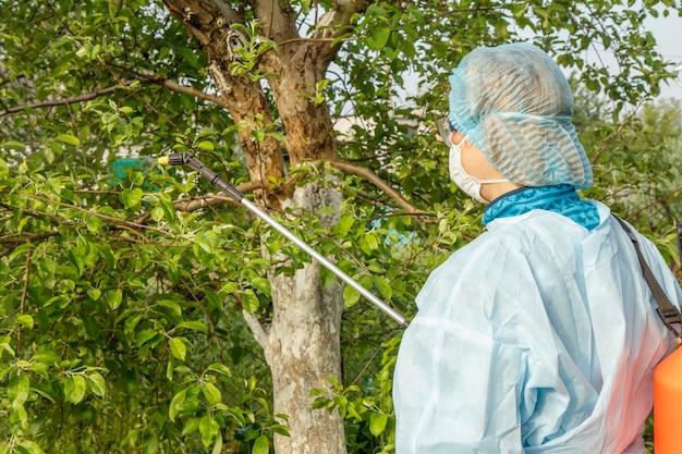 보호복과 마스크를 쓴 여성이 봄 과수원에서 압력 분무기와 화학 물질로 곰팡이 질병이나 해충에서 사과 나무를 뿌리고 있습니다.