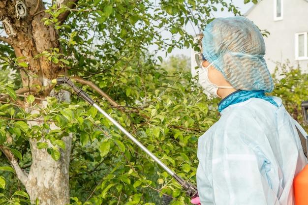 보호복을 입은 여성이 봄 과수원에서 곰팡이 질병이나 해충의 사과 나무에 압력 분무기와 화학 물질을 뿌리고 있습니다.