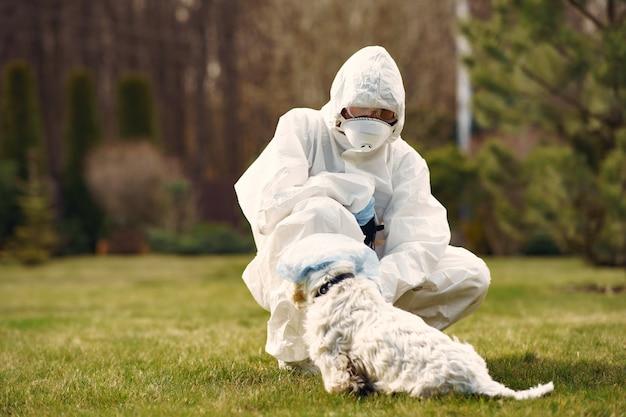 Женщина в защитном костюме гуляет с собакой