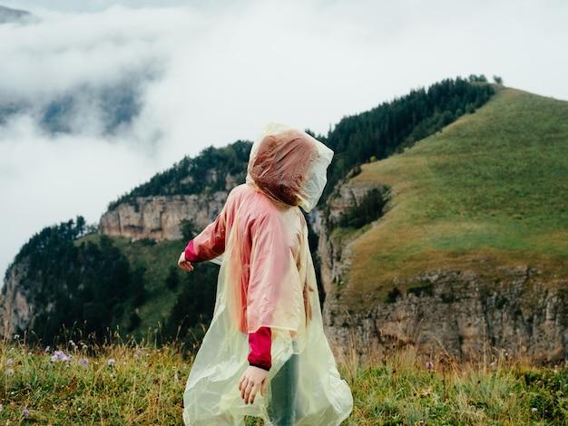 山の自然の雲の中でレインコートを着た女性が旅行します