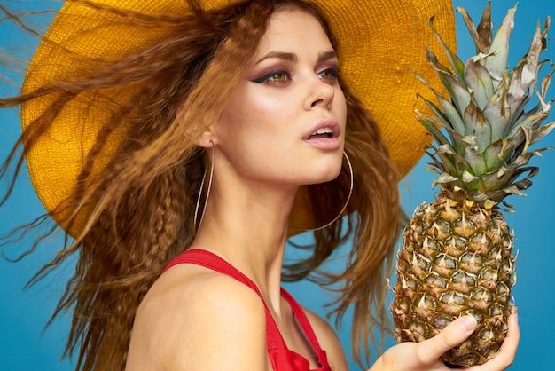 Женщина в красном купальнике и желтой шляпе позирует, горячий тропический образ с ананасом