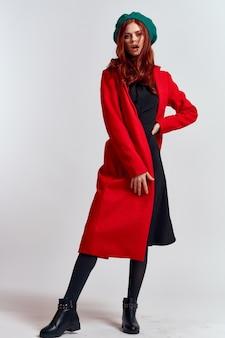 孤立した赤いコートと緑の帽子の女性