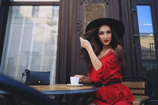 赤いドレスと一杯のコーヒーとヴィンテージの帽子の女性