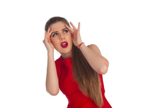 Женщина в красном платье что-то ищет на белой стене