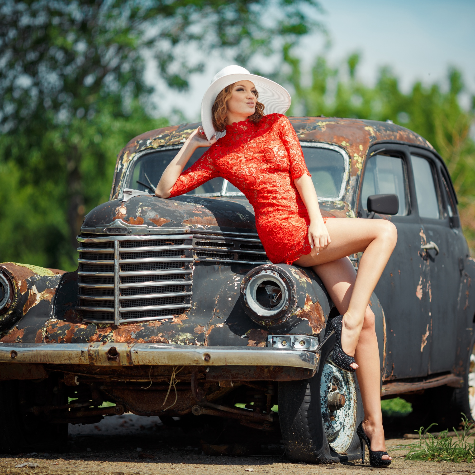 Woman in a red dress leaning against an old car