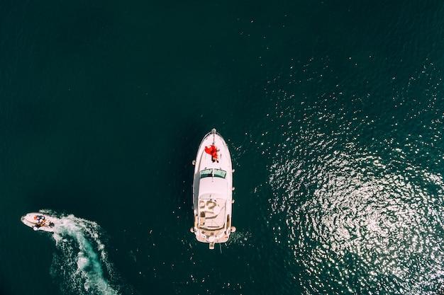 빨간 드레스를 입은 여성이 위에서 바다를 바라보며 항해하는 흰색 모터 요트의 뱃머리에 누워 있다