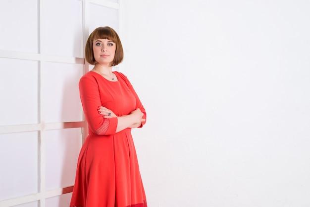 Женщина в красном платье позирует в помещении