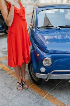 青い車のそばに立っている赤いドレスを着た女性