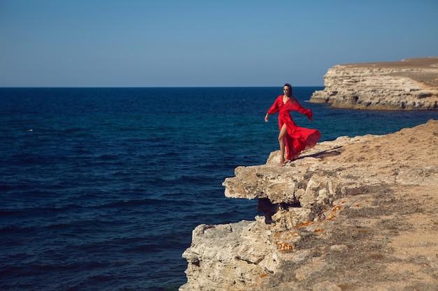 赤いドレスを着た女性が夏の崖の上の海の近くの崖に立っています
