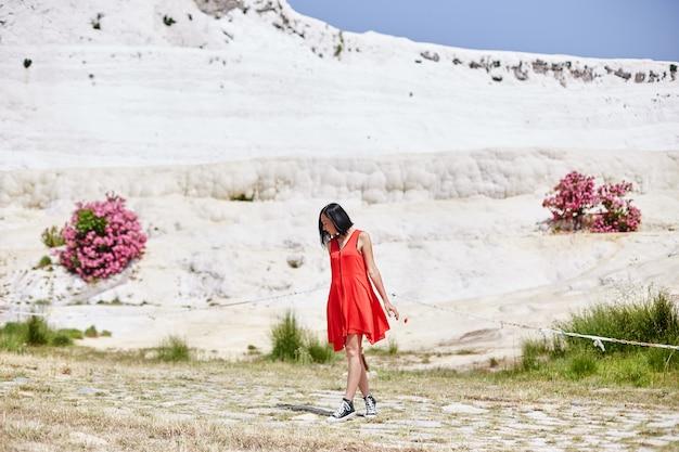 赤いドレスを着た女性がトルコのパムッカレを歩きます。