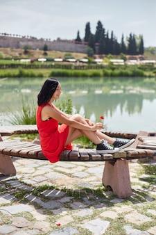Женщина в красном платье идет по памуккале, турция.