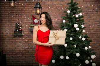 Woman in a red dress with gifts by the Christmas tree