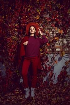 Женщина в красной шляпе и красном свитере стоит на фоне оранжевых листьев виноградной стены осенью