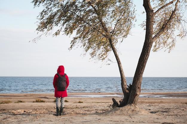 赤いジャケットを着た女性が木の下に立って波を見る