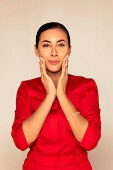 Женщина в красном медицинском костюме прикасается к лицу после обработки кожи. после увлажнения она чувствует себя более свежей.