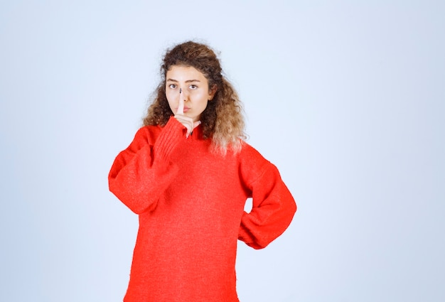 沈黙を求める赤いシャツを着た女性。