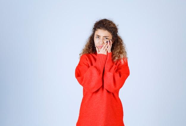 赤いシャツを着た女性は悲観的または悲しそうに見えます。