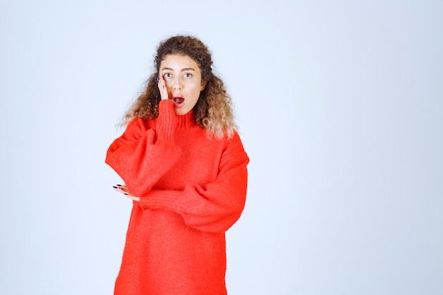 赤いシャツを着た女性は恐怖と恐怖に見えます。